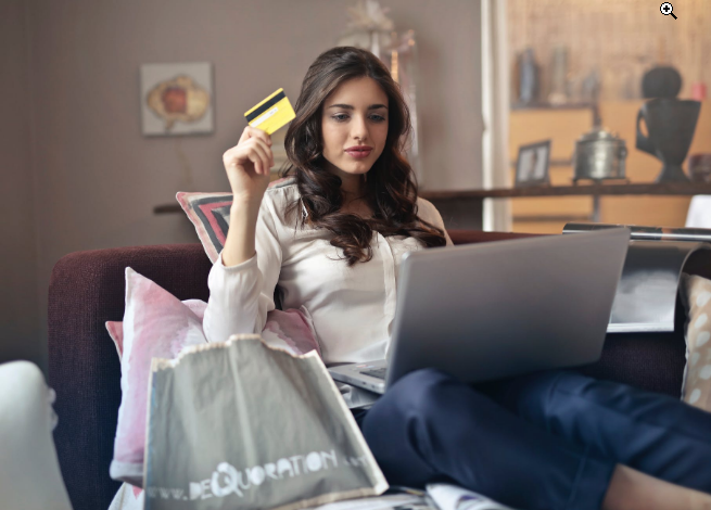 a woman holding a credit card in front of a laptop